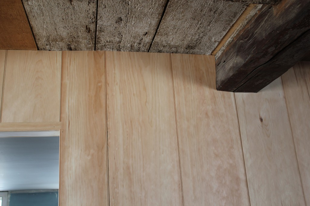 Wall paneling scribed to original joists and second story floorboards
